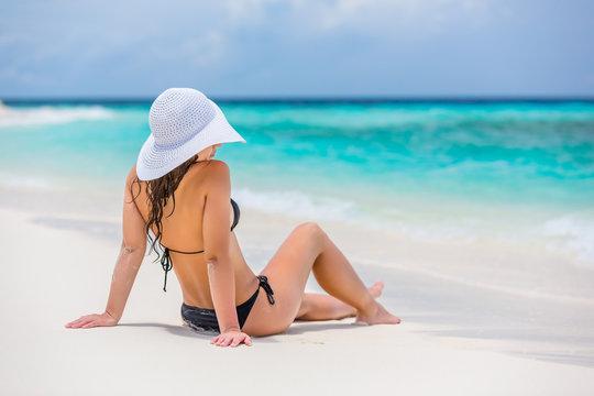Young woman in bikini sitting on the beach