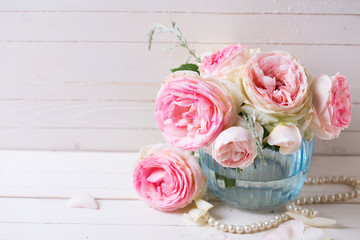 Sweet pink roses flowers  in blue vase on white painted wooden p