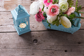 Flowers  in pink colors and candle in blue lantern  on vintage w