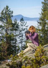 Young female photographer sitting on big rock on the mountain peak and taking picture. Trees and mountain on the background. Sunny autumn/winter day.