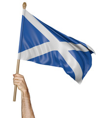 Hand proudly waving the national flag of Scotland