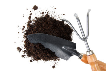 Garden tools with wooden handle in the pile of earth on a white isolated background