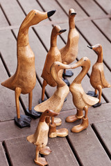 Seven hand made wooden ducks on wood background