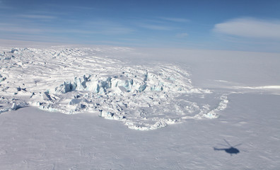 Foto auf AluDibond Arktis Aerial view of iceberg in frozen Arctic Ocean and helicopter shadow