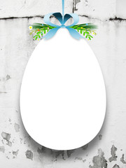 Close-up of one hanged blank Easter egg with ribbon against concrete wall background