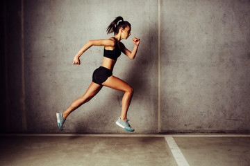 Slim attractive sportswoman running against a concrete wall
