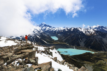 Hiker on top of mountain looking at Mount Cook