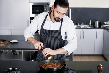 Chef preparing dishes in a frying pan