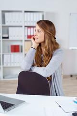 geschäftsfrau sitzt nachdenklich am schreibtisch