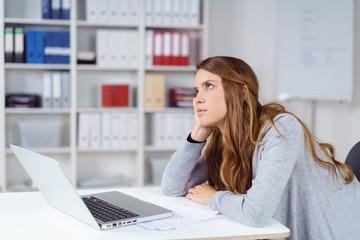 frau im büro langweilt sich und stützt den kopf auf