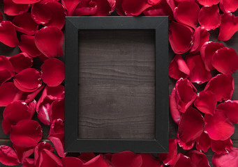 Beautiful red rose petals and frame picture are on the wooden ba