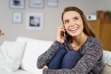 frau telefoniert mit ihrem handy in der wohnung