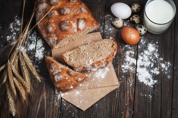Homemade bread, milk and ripe ears of rye on a wooden background, place for text