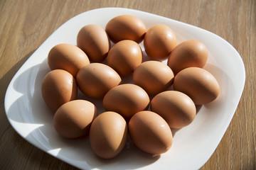 Fresh eggs in a white plate.
