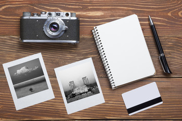 Travel, vacation concept. Camera, notepad, pen, credit card and photography on office wooden desk table. Top view with copy space for text
