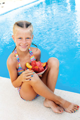 Little cute girl sitting beside the pool with a plate of ripe fr