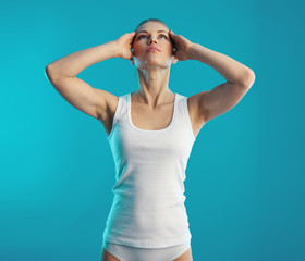 Woman training neck muscles over blue background. Relaxation and rehabilitation concept.