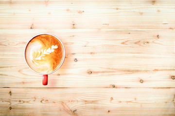 Top view cup of fresh latte art  on empty pine wood panel  background with copy space.