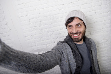 young hipster blogger man holding off screen mobile phone shooting selfie picture or video