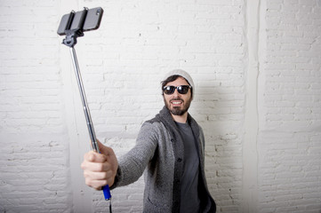 young hipster trendy blogger man holding stick recording selfie video in vlog concept