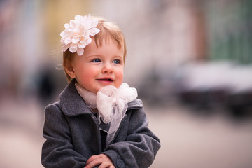 A portrait of cute little baby girl in gray coat on the street i