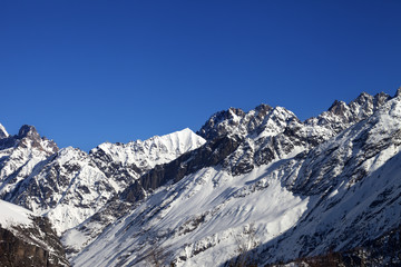 View on snowy rocks and blue clear sky at nice sun day