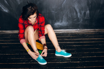 woman tying shoe laces. Ready for skateboarding
