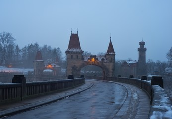Picture of the old historic and vintage stone dam from 19th century in the sunset in the winter. Dam with pitoresque watching towers and gate named Les Kralovstvi in Czech Republic, Europe.
