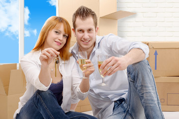 couple celebrating their new home, keys  and champagne in hand.