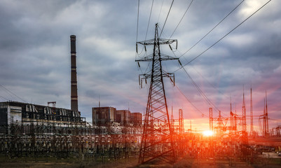 thermal power plant with pipes and power lines at sunset