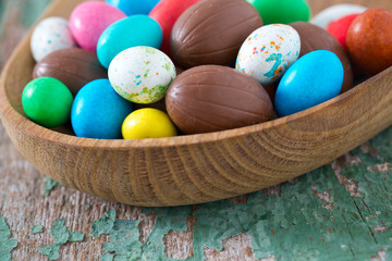 Easter candy eggs on old wooden surface