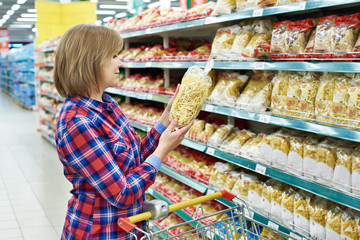 Woman with package pasta in shop