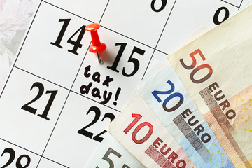 Tax day in the calendar with euro bills, close up