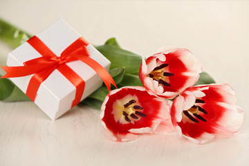 Present box with tulips on wooden background