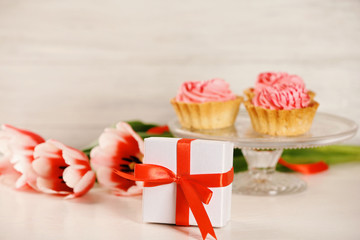 Present box with tulips and cupcakes on blurred background