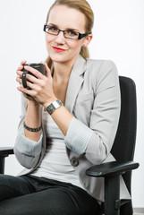 Junge Geschäftsfrau im Blazer mit Brille und Kaffeetasse