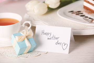Happy mother day greeting with tulips, cup of tea and present box on wooden table closeup