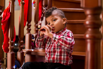 Kid plays flute on stairs.