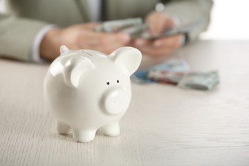 Man with money and piggy bank sitting at wooden table closeup