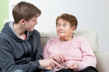 großmutter schaut mit dem enkel fotos