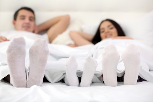 Feet of family: mother father and son in bed at home