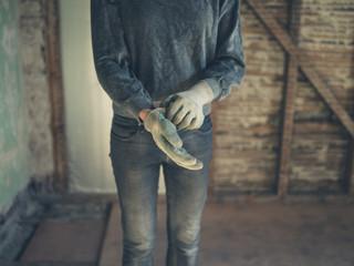 Worker putting on gloves in loft