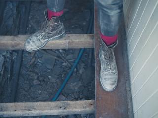Feet of worker standing on floor joists