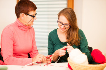 Women knitting with red wool. Eldery woman transfering her knowl