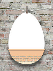 Close-up of one hanged pink decorated Easter egg blank frame with peg against weathered brick wall background