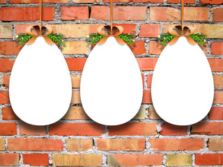 Close-up of three hanged blank Easter egg frames with ribbons against orange brick wall background