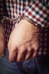 Criminal hands locked in handcuffs on dark background