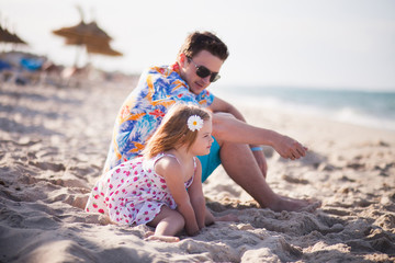 Father and daughter on the beach near the sea
