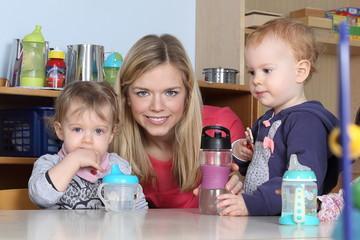 Erzieherin am Tisch Kinder trinken aus Trinkflasche mit Spielzeug 2