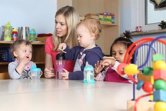 Erzieherin am Tisch Kinder trinken aus Trinkflasche mit Spielzeug